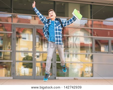 Happy teen boy with book and backpack on the first school day. Excited to be back to school after vacation. Full length outdoor portrait.