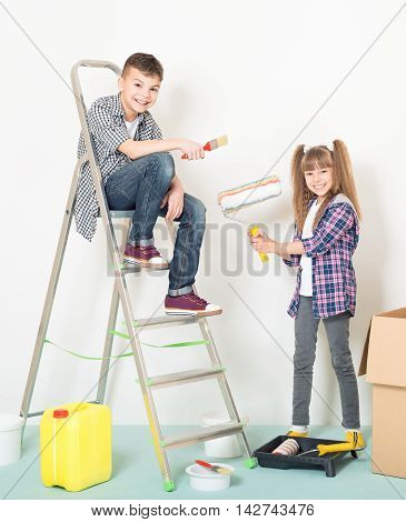 Happy children -  brother and sister, makes repairs at home. Smiling boy and girl painting wall at home.