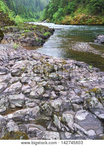 The Umqua River in Oregon flows through a solid rock bank.