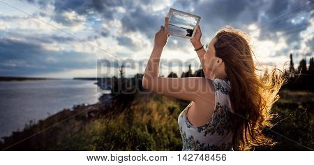 Young girl with the hair fluttering on wind photographing on digital tablet beautiful river landscape in summer evening, woman taking photo with touch pad camera during recreation time. Panoramic view