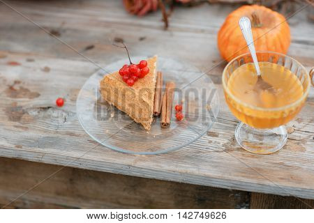 halloween inspiration. cake n wood table. Autumn still life. pumpkin, dry roses, viburnum honey cake. in a vase. twigs. on the table.