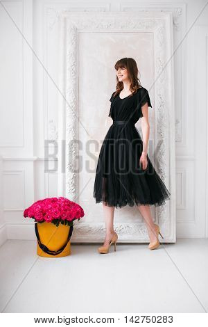 Nice young blonde girl. in a black dress and shoes on high heels. smelling flowers holding purple roses bouquet in hat box against the plastered wall.