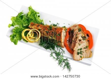 healthy dinner: grilled sea tuna fish with lemon and vegetables on white china plate isolated over white background