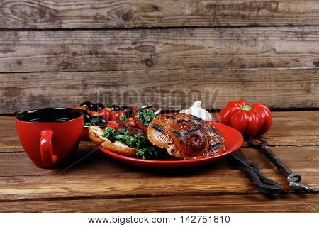 fresh grilled beef hamburger served on red plate with black coffee glass chili pepper olives green kale leaves mushroom bell garlic and forged vintage antique cutlery wooden table empty space for text