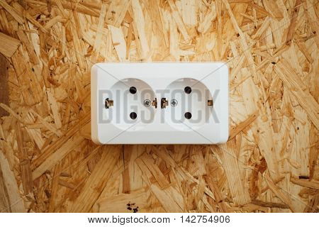 AC power socket, wooden osb wall background
