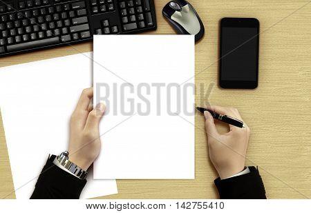 Businessman reading blank document on office desk