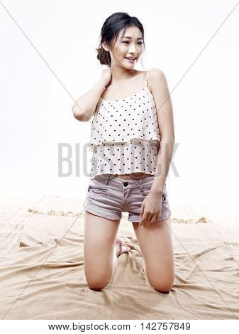 asian woman in pajamas keeling on floor isolated on white background.