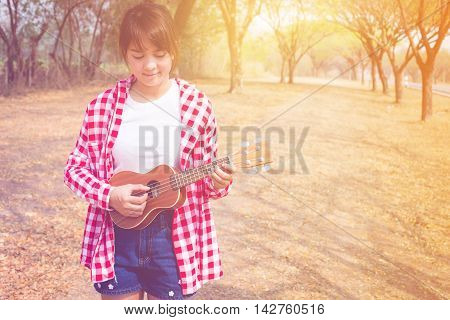 Beautiful asian woman playing ukulele guitar at outdoor in pastel and vintage style color. copy space background
