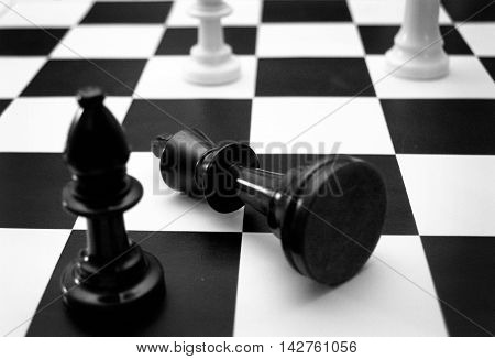 the King lays in surrender on a black and white chess board