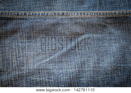 Texture of dark fabric blue jeans textile with seam. Close up detail background