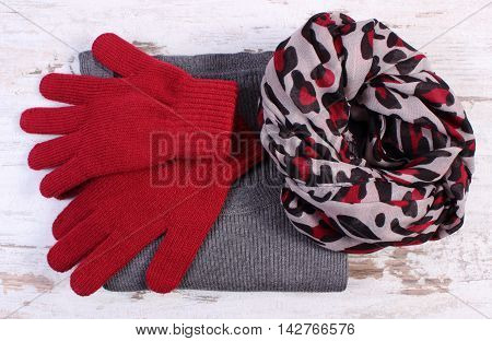 Woolen clothes for woman on old rustic board womanly accessories gloves shawl sweater warm clothing for autumn or winter