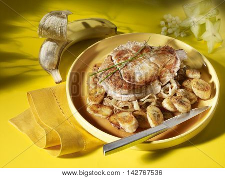 Fried Veal Caribbean with banana and star fruits on plate and tablecloth