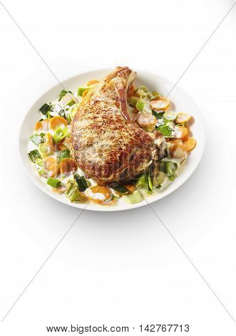 Veal chop with vegetable cream on white plate in restaurant