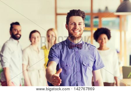 business, startup, people, gesture and teamwork concept - happy young man with beard and bow tie greeting by handshake over creative team in office