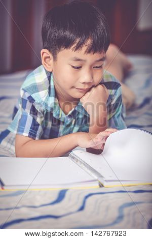 Asian Boy Reading A Book. Education Concept. Vintage Tone Effect.