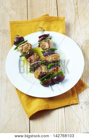 Red and green veal skewers on white plate in restaurant