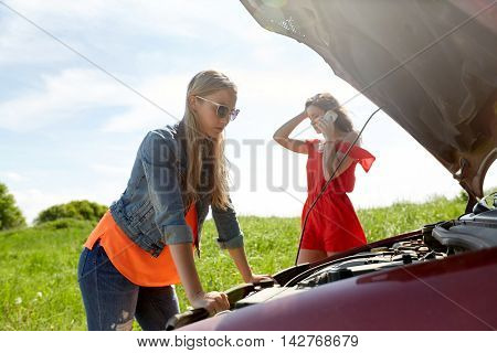 road trip, transport, travel and people concept - young women with open hood of broken car at countryside calling on smartphone to evacuation service