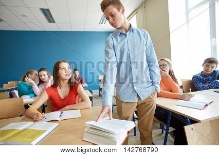 education, bullying, conflict, social relations and people concept - student boy behaving unfriendly to girl at school