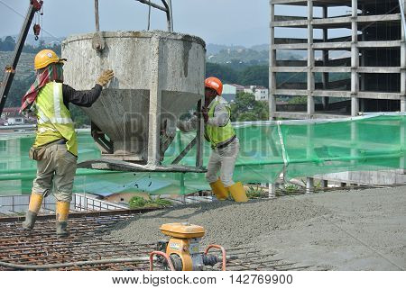 SELANGOR, MALAYSIA -JUNE 18,2016: A group of construction workers pouring raw concrete using concrete bucket into the floor slab form work at the construction site.
