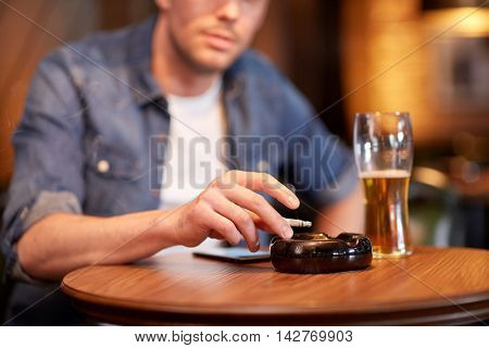 people, nicotine addiction and bad habits concept - close up of man drinking beer, smoking cigarette and shaking ashes to ashtray at bar or pub