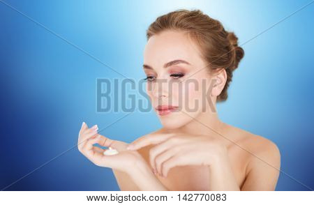 beauty, people, skincare and cosmetics concept - happy young woman with moisturizing cream on hand over blue background