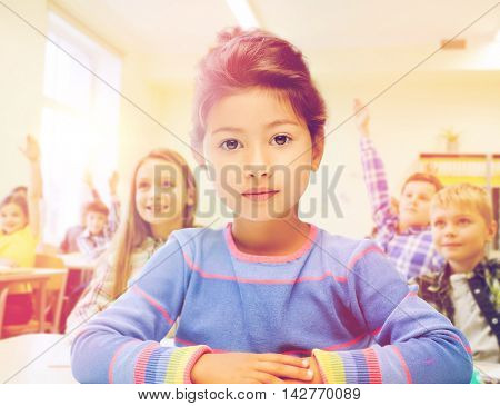 education, elementary school and children concept - little student girl over classroom and classmates background