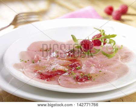 Veal carpaccio with raspberry vinaigrette on white plate