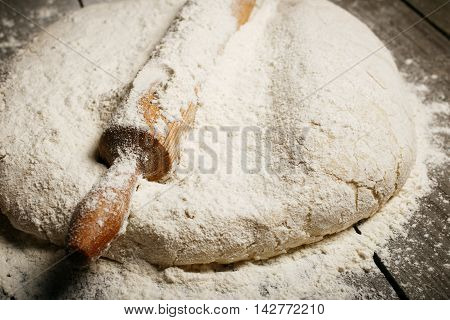 Dough with wooden rolling pin close up on wooden table with copy space