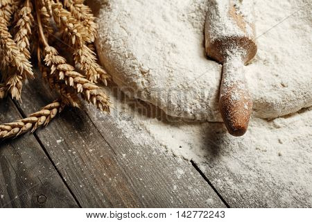 Dough with wooden rolling pin and wheat close up on a wooden table in a bakery top view with copy space