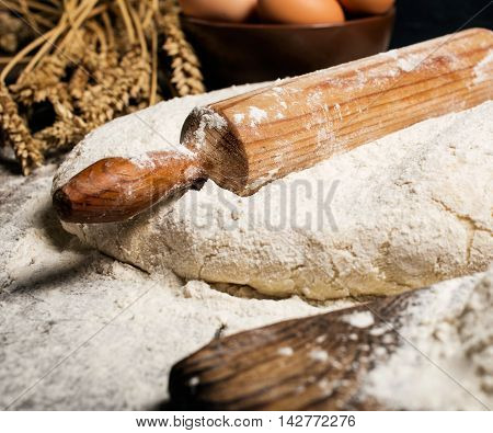 Close up dough with wooden rolling pin on wooden table