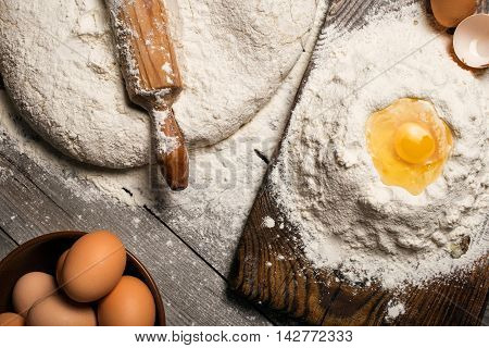 Dough with wooden rolling pin eggs and egg yolk close up on wooden table in a bakery top view
