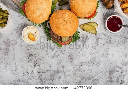 Three different burger on white rough surface top view with copy space