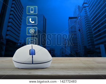 Wireless computer mouse with telephone mobile phone at and email buttons on wooden table in front of city tower background Customer support concept