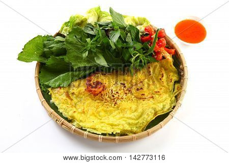 Vietnamese rice pancake or banh xeo with herbs and chili sauce on bamboo tray