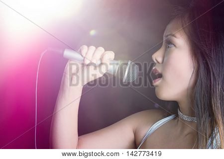 Beautiful asian woman singing into microphone