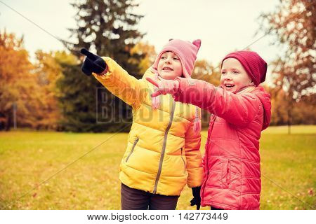 autumn, childhood, leisure, gesture and people concept - two happy little girls pointing finger to something in autumn park