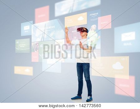 3d technology, virtual reality, entertainment, cyberspace and people concept - happy young man with virtual reality headset or 3d glasses playing game and touching screen with internet news