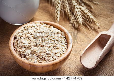 Rolled oats (oat flakes), milk and golden wheat ears on wooden background. Raw food ingredients, healthy lifestyle, cooking food, healthy food concept