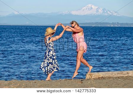 Two women on beach having fun. Centennial Beach at Boundary Bay Regional Park Tsawwassen British Columbia Canada.