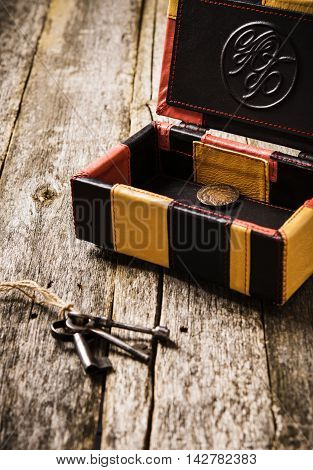 Leather box. Opened leather box with monogram and ancient coin inside on a rustic wooden background with old keys. Vintage style. Selective focus