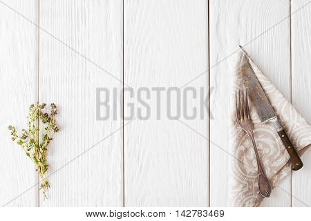 White wooden background with old cutlery, flat lay. Free space on wood with knife and fork on napkin and herb, frame