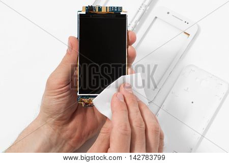 Repairman cleaning smartphone screen, taken apart case. Disassembled phone in repair service, white background, electronics recovery concept