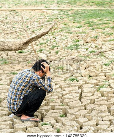 The farmer sitting on mud crack in dry season