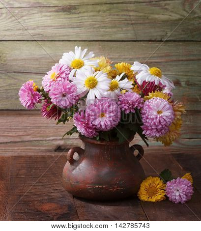 Colourful chrysanthemums bunch on old wooden table.