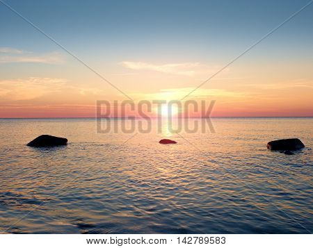 Romantic Sea. Boulders Stick Out From Smooth Sea.