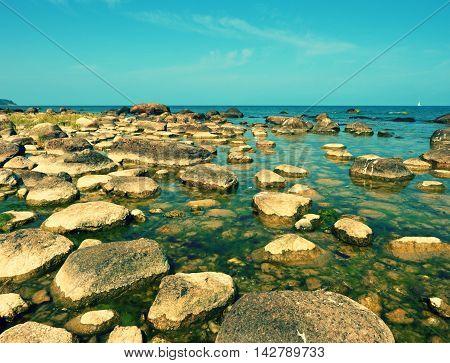 Big Boulders In Shore In  Smooth Wavy Sea. Stony Coastline