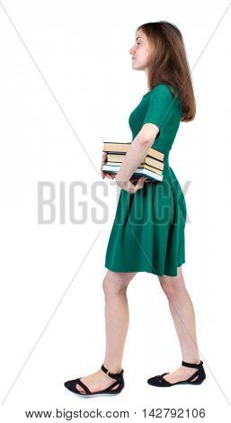 Girl comes with  stack of books. side view. Rear view people collection.  backside view of person.  Isolated over white background. The slender brunette in a green short dress is in the side with a