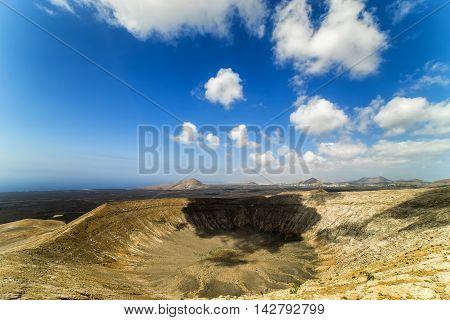 The rim of Caldera Blanca, a volcano on Lanzarote with Mancha Blanca in background, in the Spanish Canary Islands.