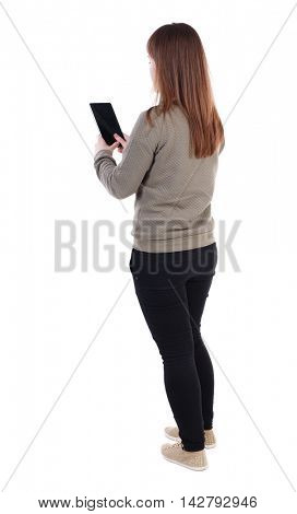 back view of standing young beautiful  woman  using a mobile phone. girl  watching. Rear view people collection.  backside view of person.  Isolated over white background. A girl in a gray sweater