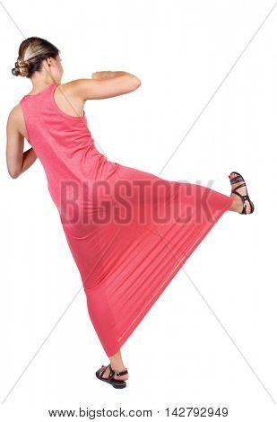 skinny woman funny fights waving his arms and legs. Isolated over white background. A slender woman in a long red dress with a sweep has foot.